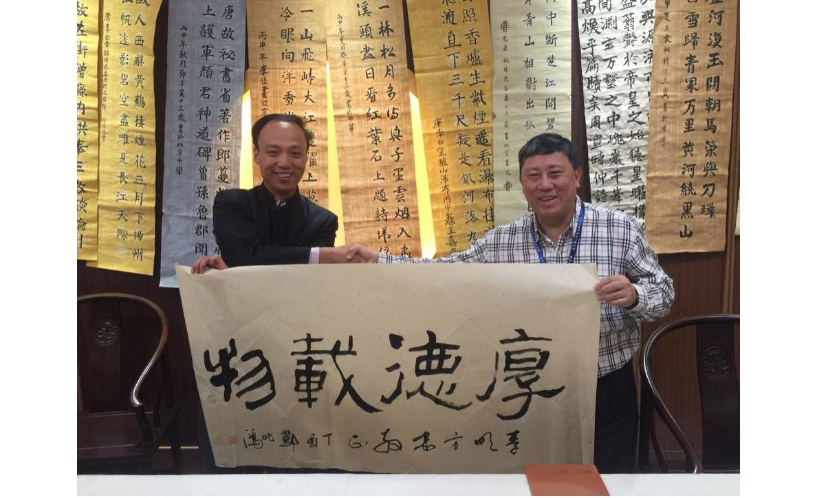 筆者參觀北京中學與李明老師書法交流。背景為學生作品。(作者提供)
