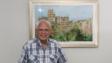 江啟明是著名畫家和美術教育家,他以細膩的畫功,描繪香港景物。圖為他在自己的作品《九龍城寨》前留影。