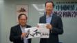 支聯會主席何俊仁致送「人民不會忘記」毛巾給丁偉博士。
