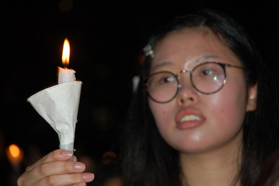燭影下戚戚然——中學女生悼念六四亡魂。賀名慧攝。
