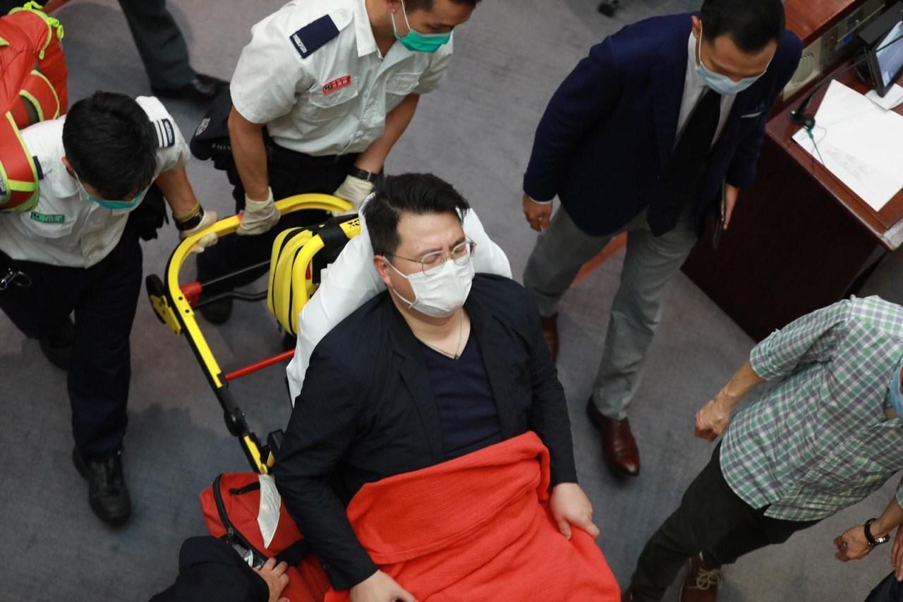 民主黨立法會議員尹兆堅懷疑不適,要用擔架床離開會議廳。