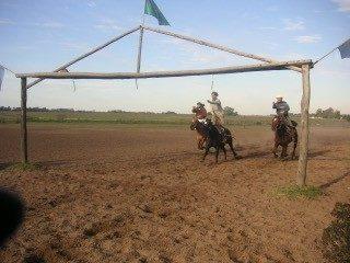 布市的馬術表演,內邊已有三個頭戴黑色西班牙帽的牛仔,手裏玩弄着一些繩索,就在這個大牧場,以索套追捕動物。