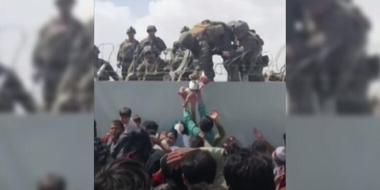 美軍手抱、「吊」起嬰孩傳入機場內的一剎那,顯現令人淚下的人道情懷。(灼見名家製圖)